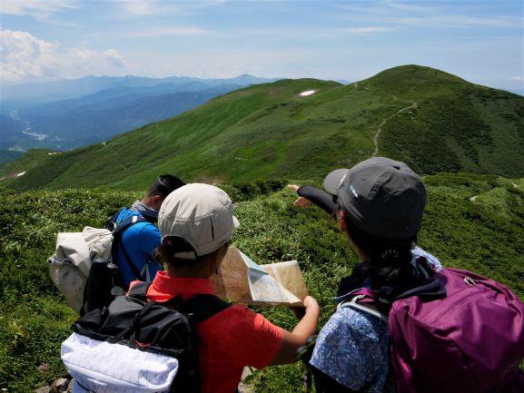 読図中。左にリフト小屋、中央に姥ヶ岳、その奥は大朝日岳?